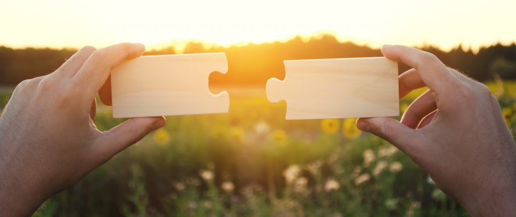 A man collects collects wooden puzzles at sunset. Concept of success, business solutions. Strategy and goal achievement. Making the right decision. Connection and partnership.