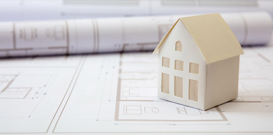 Residential building drawings and paper house model on an office desk