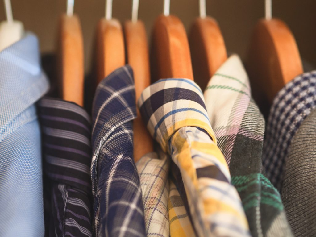 Man's closet. Hangers with shirts closeup. Male wardrobe