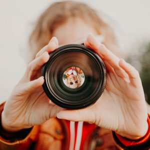 Young woman looking through camera lens.