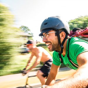 Two men riding fast on bikes and laughing